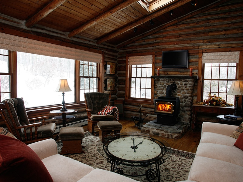 log cabin living room with fire in wood burning stove