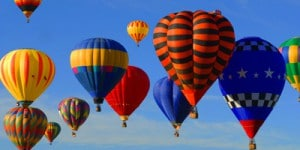 many hot air balloons against blue sky
